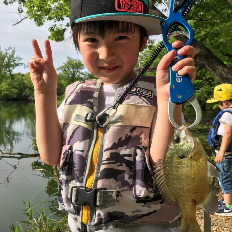 07_子どもがフィッシュグリップで魚を持っている